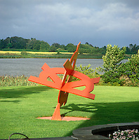 A modern sculpture catches a ray of sunshine on an otherwise overcast day