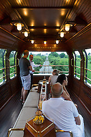 Travelling in style on the Eastern & Oriental Express from Bangkok to Singapore. Guests enjoy a drink before dinner in the observation car.