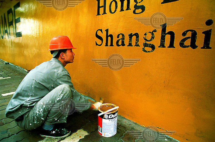 Mark Henley/Panos Pictures..China, Shanghai..Labourer looking up at 'Shanghai' written on exterior of construction site, as he paints it yellow.
