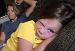 daughter making a funny face to the camera with her mother in the background in the living room