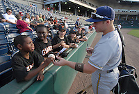 Outfielder Justin Milo (2) of the Charleston RiverDogs signs balls for young fans prior to a game against the Greenville Drive on May 27, 2010, at Fluor Field at the West End in Greenville, S.C. Photo by: Tom Priddy/Four Seam Images