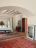 Reclaimed wood and natural Majorcan stone is used throughout the house. The bedroom is simply furnished with a green painted double four-poster bed, a chest of drawers and red patterned rugs on the tiled floor.