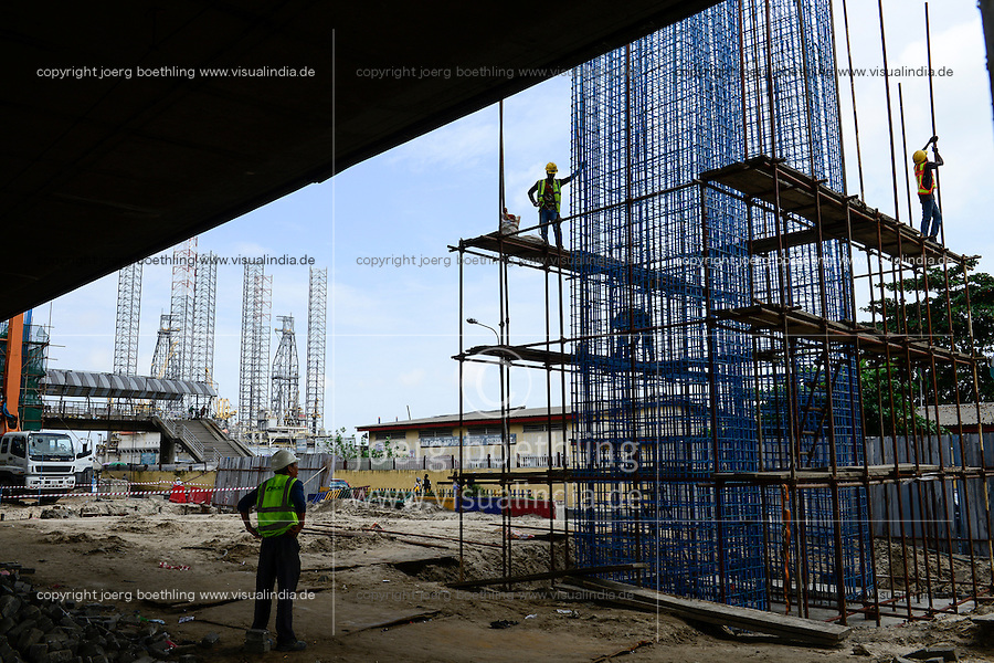 NIGERIA, City Lagos, flyover construction for new metro train by chinese company CHINA CIVIL CCECC, behind two oil platform laying in Lagos port