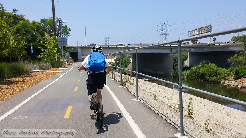 Holland barrels down the Los Angeles River Greenway Trail on his Yedoo Dragstr kick scooter during the 2017 (17th annual) Los Angeles River Ride.  Holland has just made a giant kick, and he's hunching / bending forward to be more aerodynamic as he prepares to go under the Glendale Freeway (2) bridge.