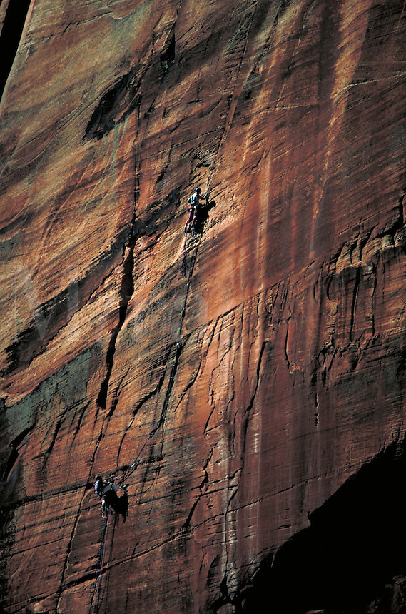 Two climbers climbing a huge sandstone face at Zion National Park. Connotations - Danger, teamwork, courage, daring, challenge. sports, geology, rock. Utah, Zion National Park.