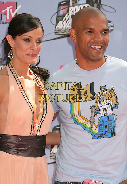 DAYANARA TORRES & AMAURY NOLASCO.2007 MTV Movie Awards held at the Gibson Amphitheater, Universal City, California, USA..June 3rd, 2007.half length coral peach orange halterneck blue tee shirt 84 transformers couple brown sash .CAP/ADM/RE.©Russ Elliot/AdMedia/Capital Pictures *** Local Caption *** ...