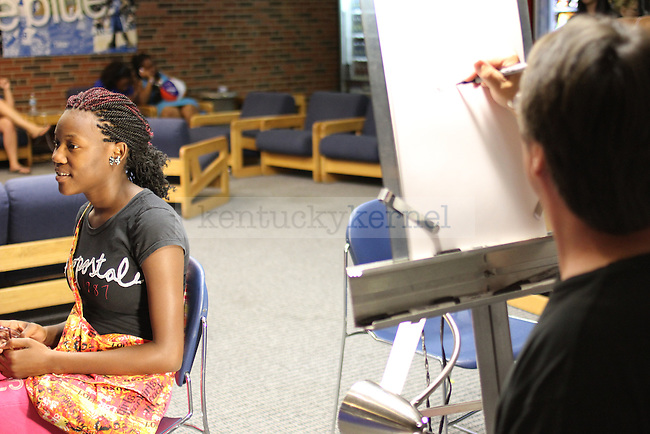 Undergraduate studies freshman Kaylin Johnson gets a caricature drawn of her at Student Center Spectacular at the Student Center on Sunday, August 19, 2012. Student Center Spectacular encouraged new students to explore the Student Center and get involved at UK. Photo by Tessa Lighty | Staff
