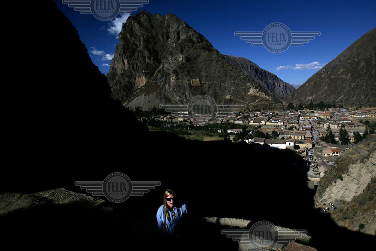 A tourist stands in a shaft of sunlight outside the town of Ollantaytambo, the 'last living Incan town'. The town was built on top of Incan ruins and incorporates its stones and even some of the original stone doors.  ..