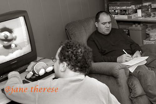 michael writes a letter to his parents as David watches Sesame Street at the group home in Robbinsville, NJ. photo by jane therese