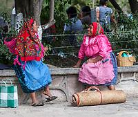 Tlacolula, Oaxaca, Mexico.  Tlacolula Plaza in front of Church, Capilla del Santa Cristo.  Zapotec Indians in Conversation.  Local Clothing Styles.