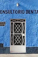 White metal door of dental practice in bright blue wall in Merida, Mexico.