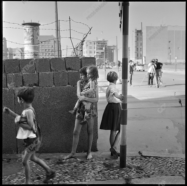 Children playing near a portion of the Berlin Wall at the time of it's construction, Friedrichstrasse near Checkpoint Charlie, West Berlin, Germany, August 1961