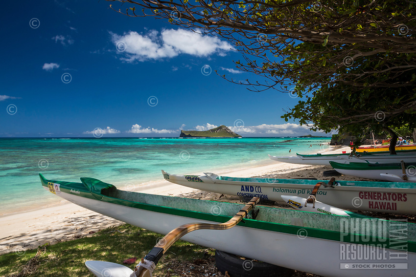 Outrigger canoes and beachgoers at Waimanalo Beach, with a distant view of Rabbit and Bird Islands, Windward O'ahu.