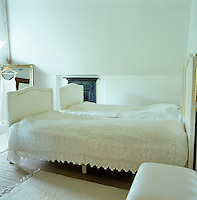 A simple white guest bedroom with twin beds covered with lace bed covers