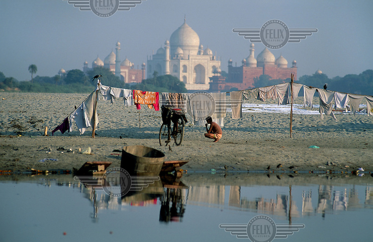 ©Mark Henley / Panos Pictures..India, Uttar Pradesh, Agra. Labour. Dhobi Wallah (Laundry man) waiting for clothes to dry on sand bank in Yamuna River with the Taj Mahal behind.