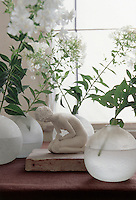 """On a window sill in the living room a tiny clay figurine entitled """"Kneeling Woman"""" by Isabelle Stienon sits surrounded by frosted glass vases filled with Phlox"""