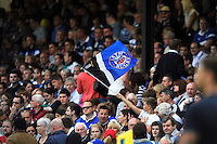 A Bath fan in the crowd waves a flag in support during the pre-match warm-up. Pre-season friendly match, between Bath Rugby and the Ospreys on August 30, 2013 at the Recreation Ground in Bath, England. Photo by: Patrick Khachfe / Onside Images