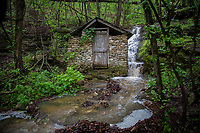 A waterfall running along an old springhouse near the Boxley Mill on the Buffalo National River in Arkansas.