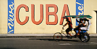 12 FEB 2003 - HAVANA, CUBA - A ciclotaxi passes a Cuba mural. (PHOTO (C) NIGEL FARROW)