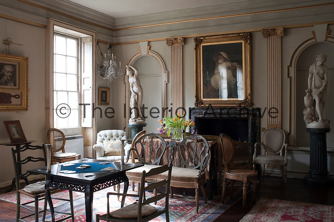 A card table is set up in the centre of the drawing room which is furnished with an assortment of antique pieces