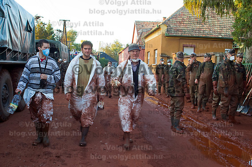 Workers walk on the street in Devecser in Hungary's Veszprem county has been flooded by toxic sludge released by a dam accident in a nearby container. The toxic chemicals left its red marking on all the walls of the houses in and out and covered all moveable belongings and streets killing people and animals. Red sludge is a waste from bauxite fefining that has a strong caustic effect. The toxic flood covered an area of over 800-1,000 hectares (1,920-2,400 acres). Seven people were killed and more than 150 injured in the disaster. Pollution from the red sludge now spread into the local rivers killing all life in rivers Marcal and Torna and now it mixed into the main European waterway river Danube. Officials say there is no risk of a biological or enviromental catastrophe there.  Devecscer, Hungary, Saturday, 09. October 2010. ATTILA VOLGYI