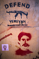 """Armenia. Yerevan. Town center. Graffiti on a wall with written words """" Defend Yerevan"""" and the address of an internet web site. Several drawings: a Kalashnikov, a fist with colorful nails and a man's portrait with a mustache. The AK-47, known as the Kalashnikov or AK, is a gas-operated, 7.62×39mm assault rifle, developed by Mikhail Kalashnikov. Yerevan, sometimes spelled Erevan, is the capital and largest city of Armenia. 12.10.2019 © 2019 Didier Ruef"""