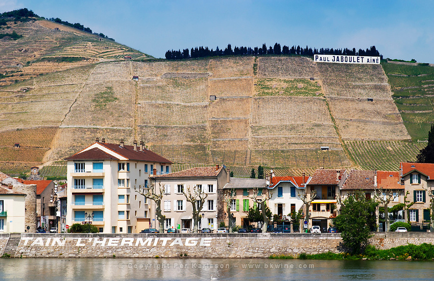 The town Tain l'Hermitage, the riverside side, the river Rhone.  The name of the town painted in large white letters   The Hermitage vineyards on the hill behind the city Tain-l'Hermitage, on the steep sloping hill, stone terraced. Sometimes spelled Ermitage.  A sign with Paul Jaboulet in the vineyard  Tain l'Hermitage, Drome, Drôme, France, Europe