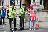 "29 June 2013, London, United Kingdom. Picture: a man in drag with a hard hat and pink high viz vest stands next to two Metropolitan police officers. Pride London 2013 parade starts with the motto ""love (and marriage)""."