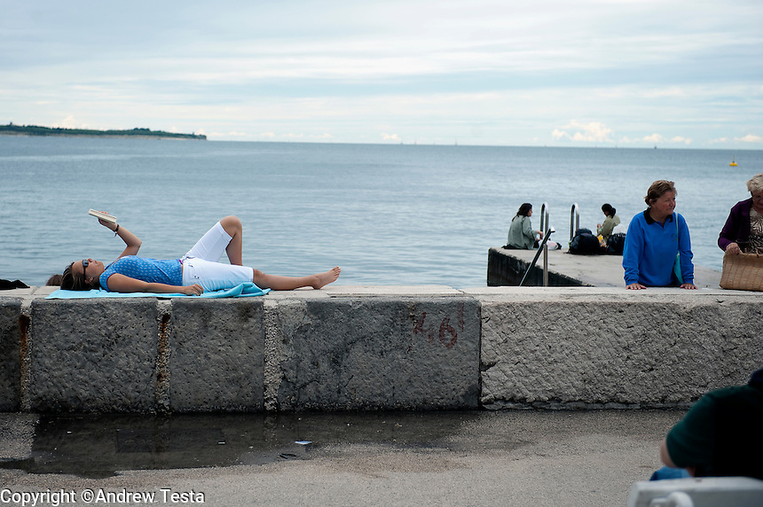 SLOVENIA. . 25th July 2011.<br /> Sunbathing on the sea wall at Piran.<br /> &copy;Andrew Testa for the New York Times
