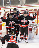 Stephanie Gavronsky (NU - 44),Rachel Llanes (NU - 11), Julia Marty (NU - 16) and Katie MacSorley (NU - 3) celebrate MacSorley's power play goal. - The Northeastern University Huskies tied Boston University Terriers 3-3 in the 2011 Beanpot consolation game on Tuesday, February 15, 2011, at Conte Forum in Chestnut Hill, Massachusetts.