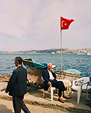TURKEY, Istanbul, portrait of a fisherman sitting with Turkish flag beside it