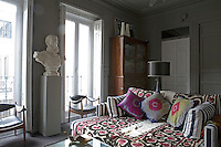 In the living room of Gaspar Sobrino's Madrid apartment, watched over by a white marble bust of Alfonso XII, the luxuriously deep sofa is strewn with antique Indian textiles in black, white and fuschia