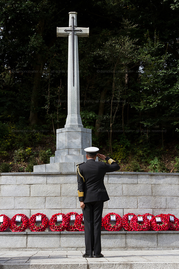 A man in military uniform salutes The Cross of Sacrifice during the Remembrance Sunday ceremony at the Hodogaya, Commonwealth War Graves Cemetery in Hodogaya, Yokohama, Kanagawa, Japan. Sunday November 11th 2018. The Hodagaya Cemetery holds the remains of more than 1500 servicemen and women, from the Commonwealth but also from Holland and the United States, who died as prisoners of war or during the Allied occupation of Japan. Each year officials from the British and Commonwealth embassies, the British Legion and the British Chamber of Commerce honour the dead at a ceremony in this beautiful cemetery. The year 2018 marks the centenary of the end of the First World War in 1918.