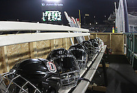 Nebraska-Omaha's helmets line the bench prior to the outdoor game against North Dakota at TD Ameritrade Park in Omaha, Neb., Saturday, Feb. 9, 2013. (Photo by Michelle Bishop)