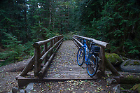 """Big Blue"" Mountain Bike At Rest On Wooden Footbridge Over Marten Creek, Taylor River Road, Mt. Baker Snoqualmie National Forest, Washington, US"
