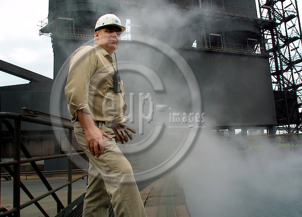 DUISBURG - GERMANY  26.  AUGUST. 2005. A worker at the Krupp steel factory  looking into a pit of steaming water. Krupp is centered by Duisburg in Germanys Ruhr district the traditional mining and steel area .. Photo: Uffe Noejgaard / EUP-IMAGES
