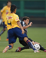 DC United defender Marc Burch (4) slides to defend the play against Monarcas Morelia defender Diego Martinez (4). Monarcas Morelia tied DC United 1-1 in the SuperLiga opening match in group B, at RFK Stadium in Washington DC, Wednesday July 25, 2007.