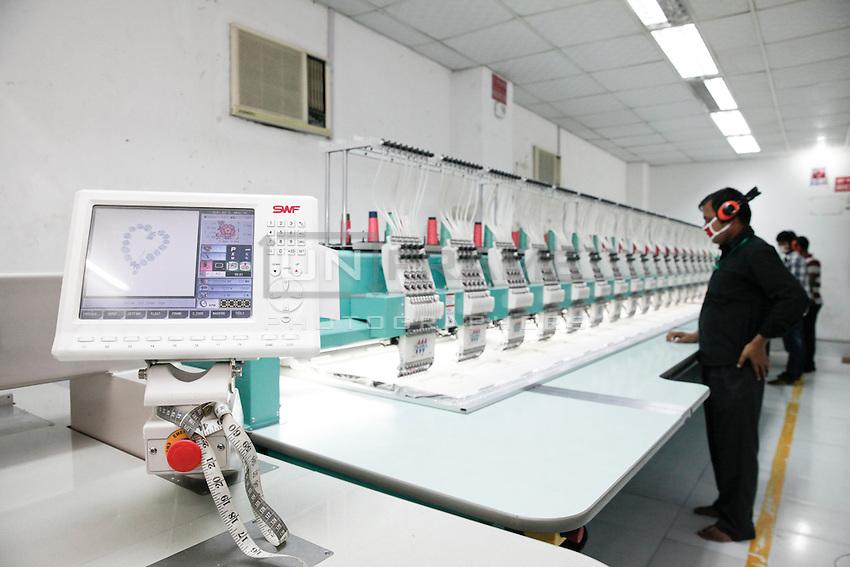 A Bangladeshi garments worker working with Computerized Embroidery Machine. Gazipur, near Dhaka, Bangladesh