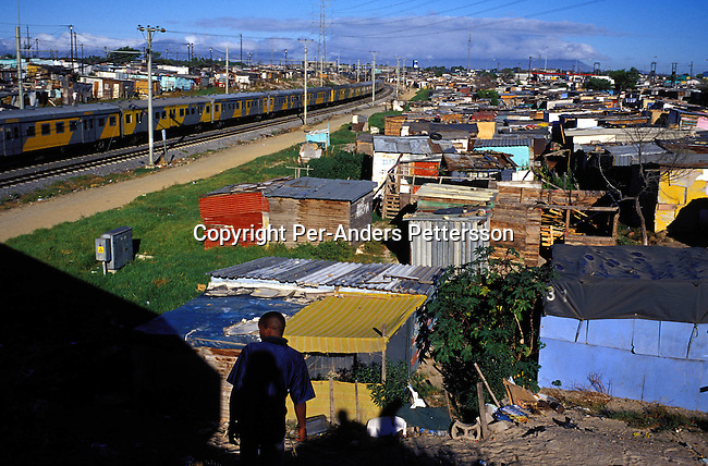 ditown00011Township A commuter train leaving Nonqubela train station for Cape Town on August 20, 2001 in Site B Khayelitsha, a township about 35 kilometers outside Cape Town, South Africa. Transport. train, electricity, shacks, .Photo: Per-Anders Pettersson/ iAfrika Photos.