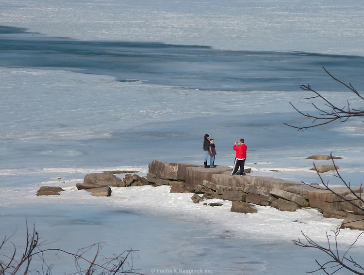 A family takes photos with the backdrop of a frozen Lake Erie.