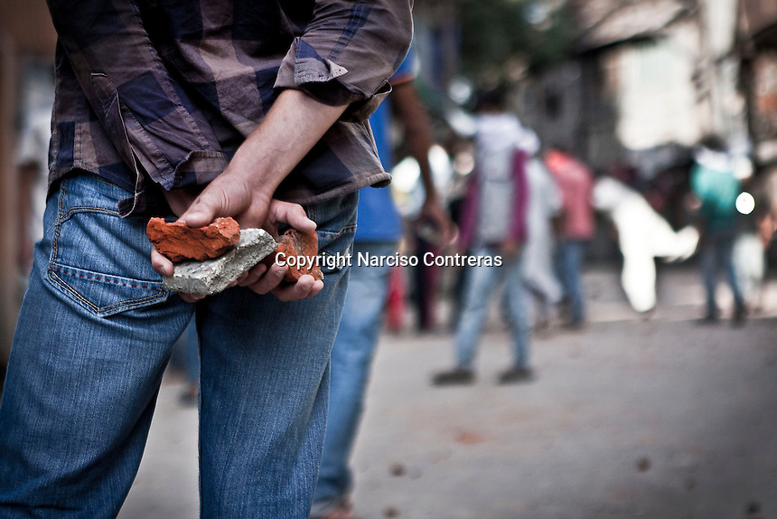 A Kashmiri muslim protester holds stones durnig a stone pelting with the paramilitary indian force in downtown of Srinagar. Outcry sparks in Nowhatta area against the detention of a kashmiri boy by police.