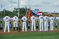 Charlotte Stone Crabs players Moises Gomez (21), Carl Chester (9), Tyler Frank (5), Zach Rutherford (15), Russ Olive (34), Tanner Dodson (10), and Zacrey Law (6) during the national anthem before a Florida State League game against the Fort Myers Miracle on April 6, 2019 at Charlotte Sports Park in Port Charlotte, Florida.  Fort Myers defeated Charlotte 7-4.  (Mike Janes/Four Seam Images)