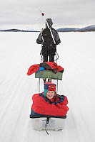 "Sweden, SWE, Kiruna, 2006-Apr-16: Sledging in Lapland: A four years old girl sitting in a ""Pulka"" is being pulled over the frozen Holmajarvi lake by her skiing mother."