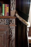 A detail of one of the 17th century carved panels that were used to construct the bookcases in the library