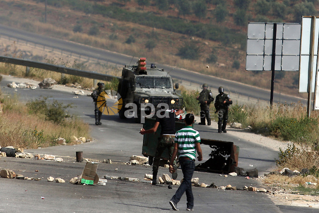 Palestinian protesters hurl stones during clashes between stone throwers and Israeli soldiers in the West Bank village of Nabi Saleh, near Ramallah, on May 25, 2012 following a protest against the confiscation of Palestinian land to expand the nearby Jewish settlement of Hallamish. Photo by Issam Rimawi