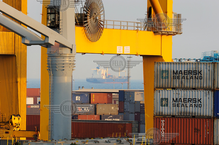 Containers on dockside at Algeciras Port, witha ship heading out into the Strait of Gibraltar behind.
