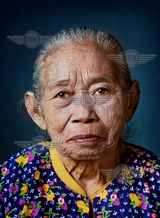 """Ronashi (born 1931) was one of tens of thousands of 'comfort women' forced into prostitution by the Japanese military during World War II..As a 13-year-old girl, Ronashi was picked up on her way home from school by a soldier nicknamed 'Sideburns' and locked up in nearby barracks. There she was raped systematically for three months by Sideburns and his pal. Her father visited the barracks several times and in vain offered himself as free labour in exchange for his daughter's release. Not until the end of the war was Ronashi, very thin by then, released. """"I had to crawl home, I couldn't even walk anymore, I hurt all over."""" Immediately after the war she underwent surgery for her internal injuries. """"I only married late because I first wanted to think. My wounds hadn't healed yet, I was afraid, I wanted to get better first."""" She has been married five times, divorced several times after just a few months and has never been able to bear children. """"I did get injections from the doctor, but it's God who determines whether you have children, not people."""" Since the death of her last husband she lives alone, in a small hut, with a few chickens and a goat. """"When rice is planted or harvested, I work in the fields, otherwise I sell baked cassavas or bananas. And the grandchildren of my aunt also sometimes give me a little rice.""""."""