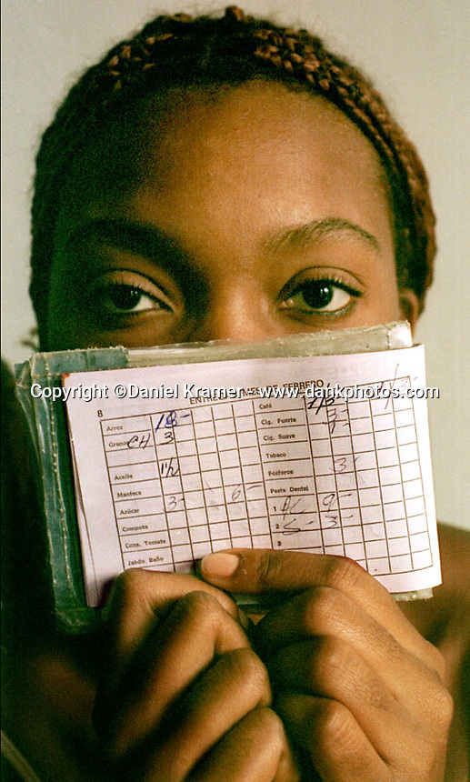 A woman (who preferred to remain anonymous) holds her ration book in 2000. Cuban's receive small monthly allotments of food, cigarettes, cigars and coffee.