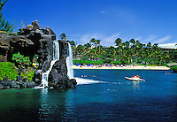 Tourists on a pontoon boat enjoy the blue lagoon and cascading waterfall at the fabulous Hilton Waikoloa Village resort on the Big Island of Hawaii.