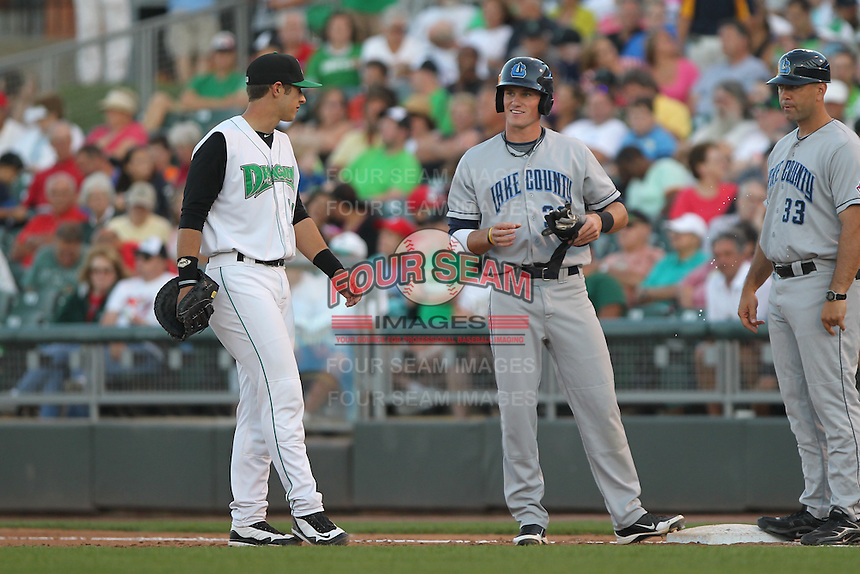 Lake County Captains outfielder Jordan Smith #39 talks with Dayton Dragons first baseman Nick O'Shea #23 during a game at Fifth Third Field on June 25, 2012 in Dayton, Ohio. Lake County defeated Dayton 8-3. (Brace Hemmelgarn/Four Seam Images)